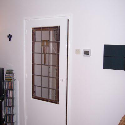 het gemaakte glas in lood is geplaatst in de vermaakte deur